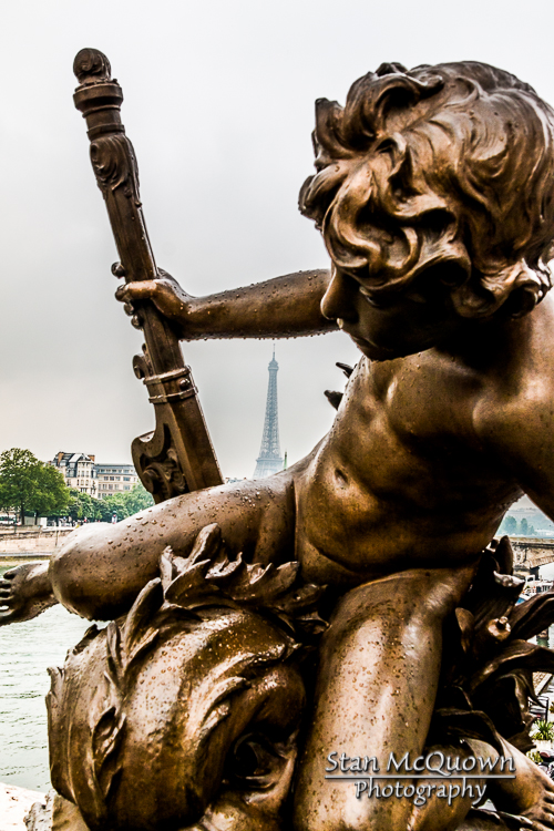 Eiffel Tower in background through one of the ornate statues of the Pont Alexandre III.